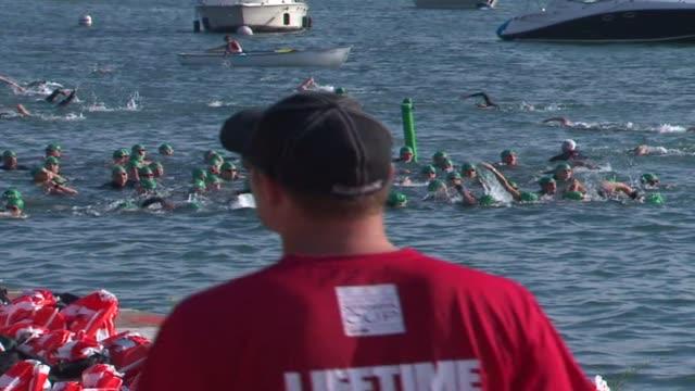 vídeos de stock, filmes e b-roll de start of the swimming leg of a triathlon on august 27 2012 in chicago illinois - touca de natação