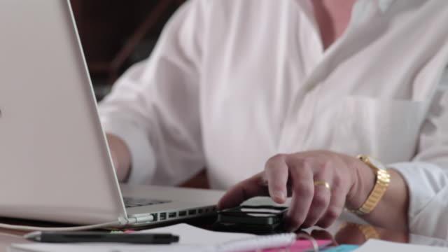 vídeos de stock, filmes e b-roll de start up business, man in dining room with laptop, tilt up, phone conversation.  - só um homem maduro