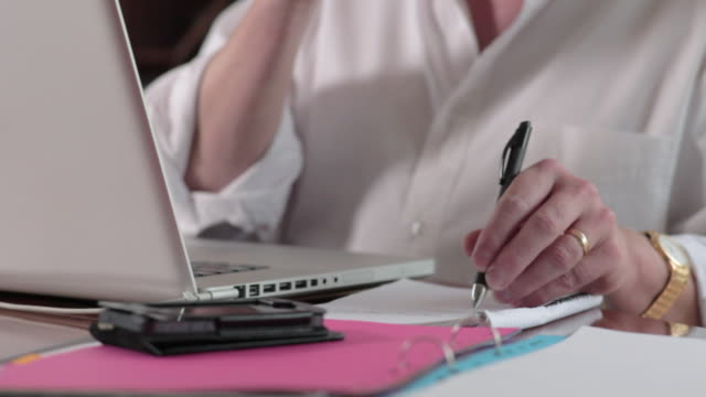 vídeos y material grabado en eventos de stock de start up business, man in dining room with laptop, writing, thinking, tilt up. - a la izquierda de