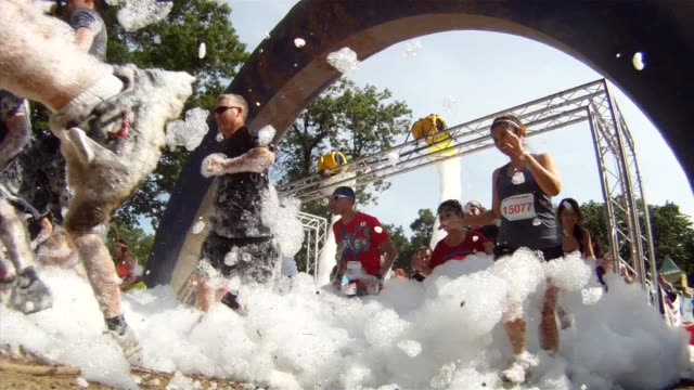 vidéos et rushes de starters run through foam to get going foam fest two shots - salmini