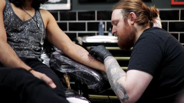 starting an arm tattoo - tatuaggio video stock e b–roll