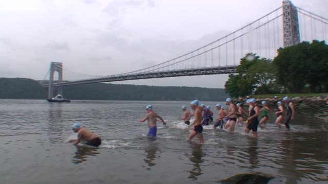 starting at the little red lighthouse below the george washington bridge swimmers head into hudson for a five mile swim to lower manhattan split... - salmini stock videos and b-roll footage
