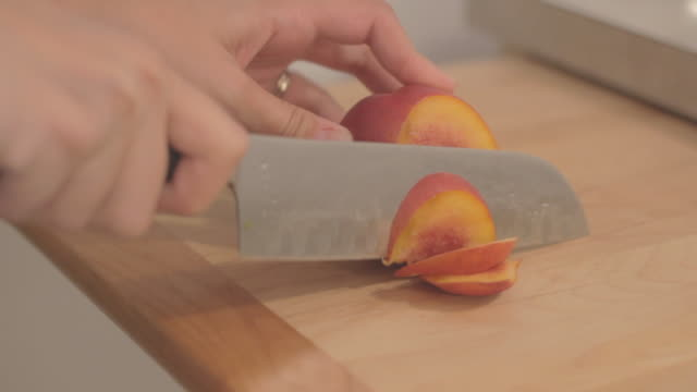 starting to cut a peach into large slices on a blue cutting board from top view. - モモ点の映像素材/bロール