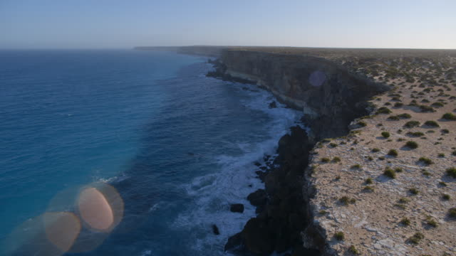 Startling flat landscape meets the calm blue waters of the South Australian coast (with lens flare).
