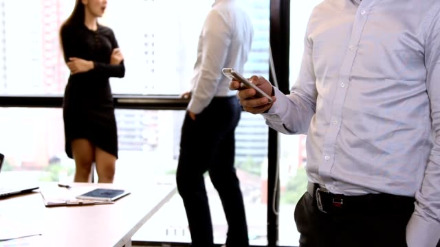start-up meetings :the officer holding mobile phone about check data before discuss in meeting room with full hd video format. - sending stock videos and b-roll footage