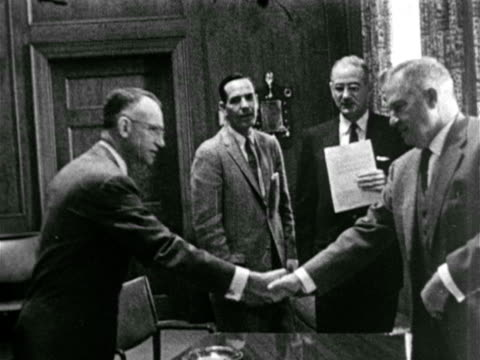 State Capitol building VS Governor Earl K Long meeting w/ group of men in office shaking hands posing seated w/ men BG VS Earl at desk PAN Earl to...