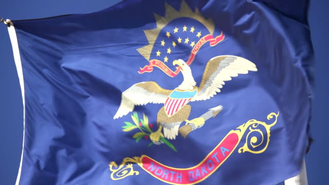 state flag of north dakota waving in the breeze - 4k/uhd - bismarck north dakota stock videos & royalty-free footage