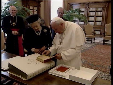 state gifts on display; lib italy: rome: the vatican: queen standing with pope john paul ii as pope presenting her with gift of 13th century copy of... - pope john paul ii stock videos & royalty-free footage