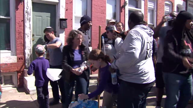 vídeos y material grabado en eventos de stock de state of emergency declared in baltimore shows exterior shots volunteers in the streets helping to clean up a neighbourhood on april 28 2015 in... - injusticia