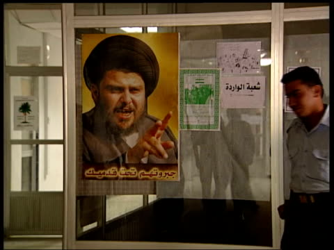 state of emergency declared in basra tx iraqi police officer along to kiss poster of militant cleric moqtada alsadr and giving thumbs up gesture - muqtada al sadr stock videos & royalty-free footage