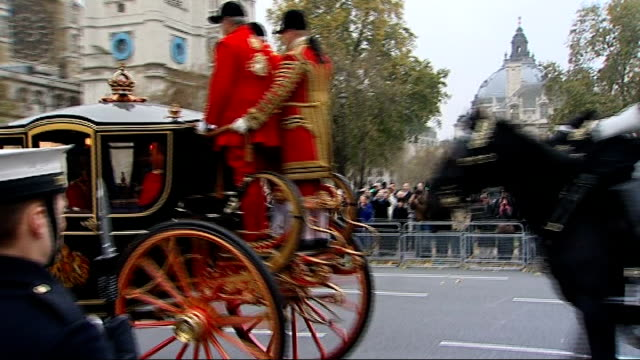 queen carriage procession along royal navy sailors and royal marines lining the street / carriage procession of queen elizabeth ii and prince philip... - the queen's speech state opening of uk parliament stock-videos und b-roll-filmmaterial