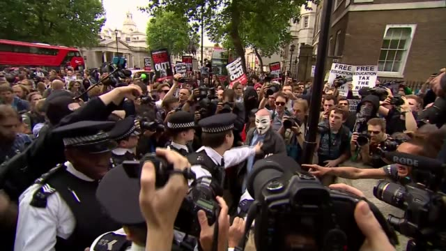 vídeos y material grabado en eventos de stock de queen's speech 2015 england london whitehall large group of antiausterity protesters one wearing 'v for vendetta' face mask held back by line of... - placard