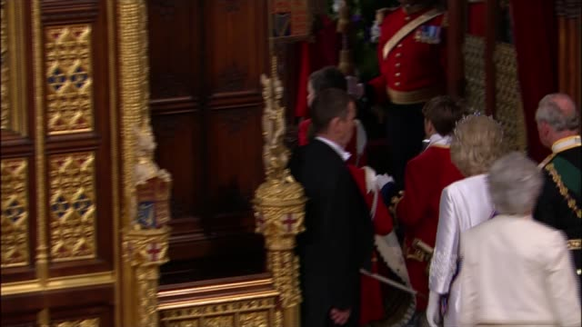 state opening of parliament: queen's speech 2015; queen and prince philip standing and leaving house of lords / members of house of lords chatting at... - the queen's speech state opening of uk parliament stock videos & royalty-free footage