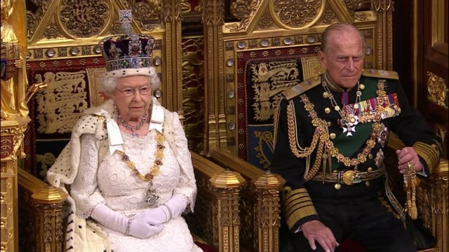 queen's speech 2015 queen and prince philip awaiting arrival of mps from house of commons and queen handed speech - the queen's speech state opening of uk parliament stock-videos und b-roll-filmmaterial