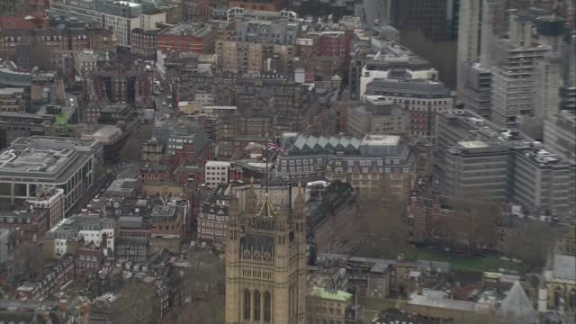 westminster aerials via bbc england london houses of parliament and river thames / union jack on victoria tower / - victoria tower stock videos & royalty-free footage
