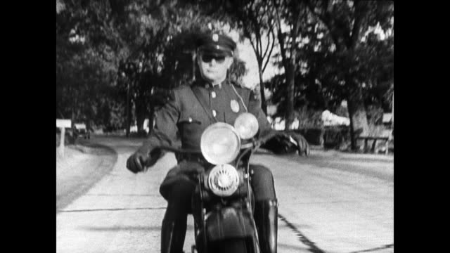 vídeos de stock e filmes b-roll de state policeman on motorcycle in residential area state motorcycle policeman following behind convertible car state policeman - 1935