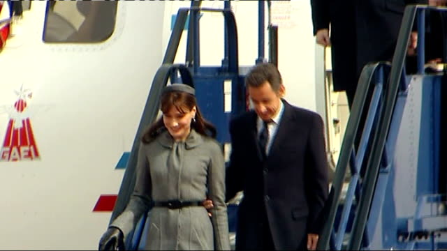 state visit by nicolas sarkozy and his wife carla bruni; england: london: heathrow airport: ext nicolas sarkozy down steps from plane with his wife... - british royalty stock videos & royalty-free footage
