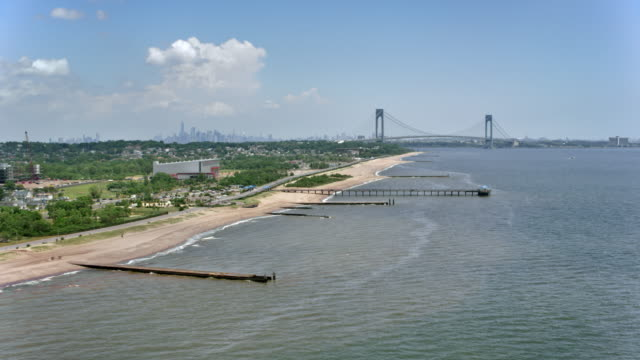 aerial staten island with verrazano-narrows bridge in the distance on a sunny day - staten island stock videos and b-roll footage