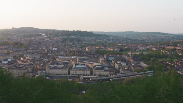 a static aerial establishing shot of the town of bath uk showing buildings in the city center surrounded by green conutryside - establishing shot stock videos & royalty-free footage