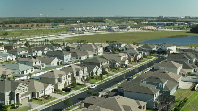 static aerial shot of suburban homes in florida with new construction in distance - stereotypically middle class stock videos & royalty-free footage