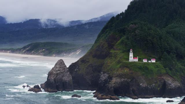 static aerial shot of waves crashing around heceta head lighthouse - heceta head stock videos & royalty-free footage