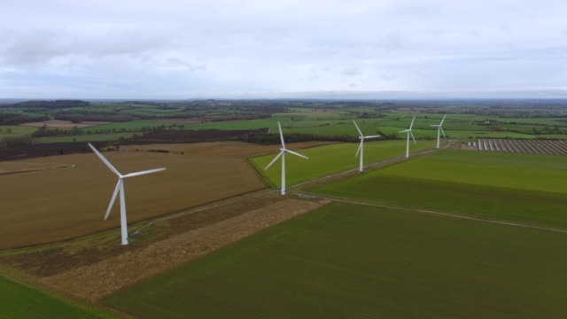 static aerial view of a line of wind turbines spinning - wind power stock videos & royalty-free footage