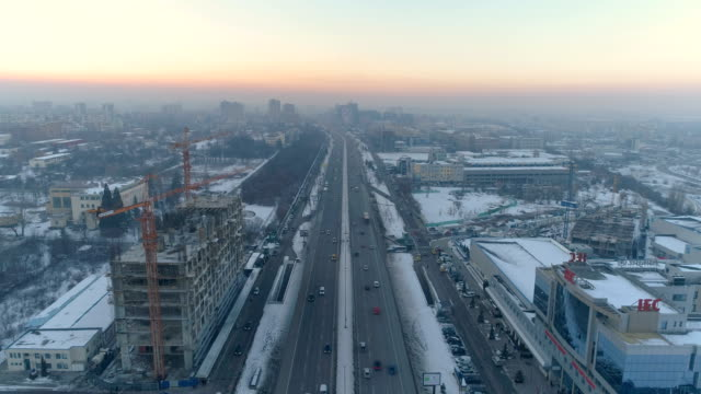 static aerial view of city traffic during snowy sunset - urban road stock videos & royalty-free footage