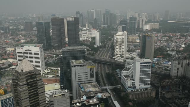 stockvideo's en b-roll-footage met static and pan of commercial buildings and residential homes stand in light smog in jakarta, indonesia, on tuesday, june 18 commercial buildings and... - financieel district