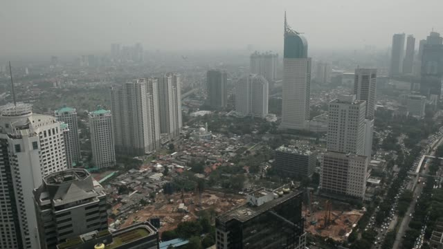 Static and pan of Commercial buildings and residential homes stand in light smog in Jakarta Indonesia on Tuesday June 18 Commercial buildings and...