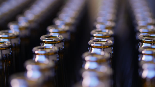 static close up of rows of empty brown glass bottles - beer bottle stock videos & royalty-free footage