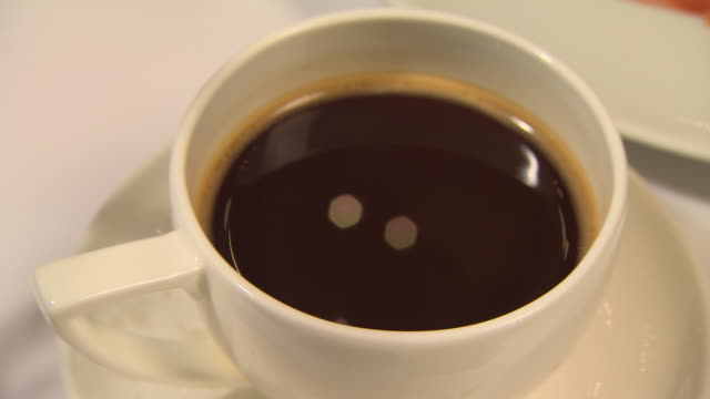 static, close-up shot of coffee quivering in a cup and saucer. - coffee cup stock videos & royalty-free footage