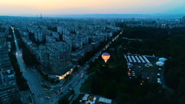Static drone in the night city sky looking at horizon and at public park with balloon with hot air