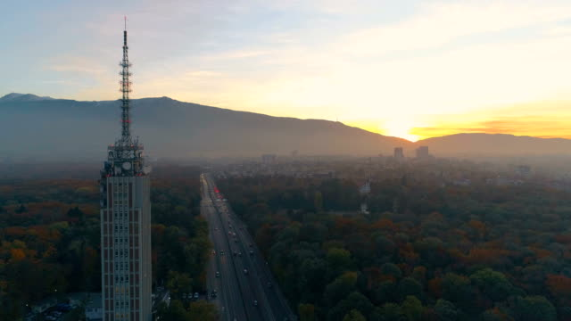 static drone shot aerial view looking at beautiful sunset view over the big city traffic - bulgaria stock videos & royalty-free footage
