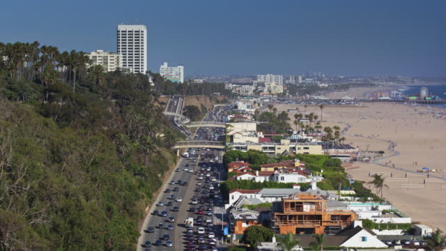static drone shot looking across santa monica towards the pier - palisades park stock videos & royalty-free footage