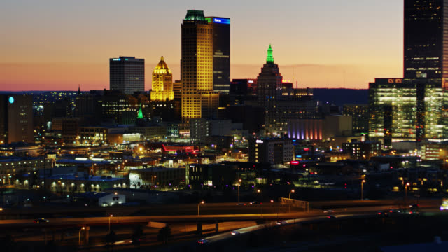 static drone shot of downtown tulsa lit up at nightfall - oklahoma stock-videos und b-roll-filmmaterial