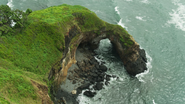 static drone shot of natural stone arch on oregon coast - oregon coast stock videos & royalty-free footage