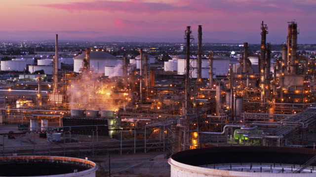 static drone shot of oil refinery surrounded by industrial area and los angeles sprawl - refinery stock videos & royalty-free footage
