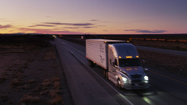 static drone shot of trucks on interstate at sunset - american interstate stock videos & royalty-free footage