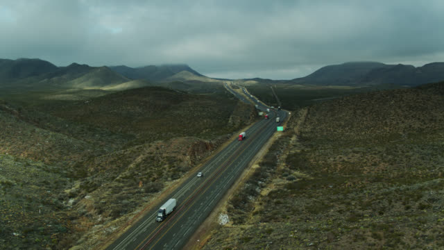 static drone shot of trucks on interstate in west texas - interstate 10 stock videos & royalty-free footage