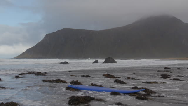 stockvideo's en b-roll-footage met static establishing shot of a surfboard on a beach in norway on september 30, 2018. - sport