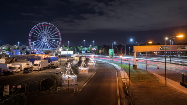 vidéos et rushes de a static ferris wheel in a closed travelling funfair stands silent as rapidly moving traffic travels along a busy road - véhicule utilitaire léger