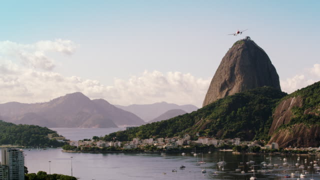 Static, high definition, shot of an airplane flying over Guanabara Bay - Rio de Janeiro, Brazil.