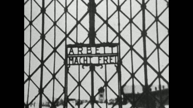 static medium shot of the 'arbeit macht frei' sign over the gate of dachau concentration camp in upper bavaria, germany; 1966. - capital letter stock videos & royalty-free footage