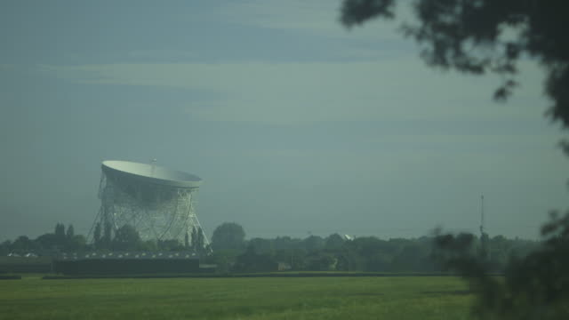static medium shot showing the scale of the lovell telescope radio dish at the jodrell bank observatory in lush green surroundings in cheshire, uk. - bank stock-videos und b-roll-filmmaterial