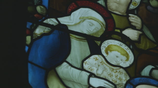 Static sequence showing the Virgin Mary with Jesus Christ as a boy and an unknown haloed figure in stained glass in an English church, UK.