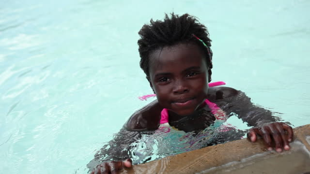 Static shot of a black child paddling in a pool.