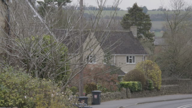 static shot of a british home behind the tree branches at long compton - bin stock videos & royalty-free footage