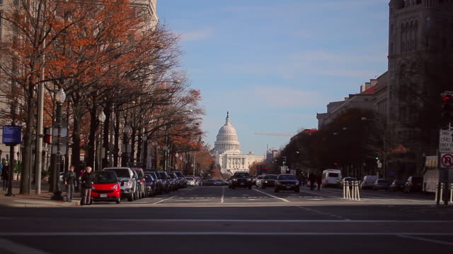 A static shot of a busy road in front of the US Capitol building during the daytime.