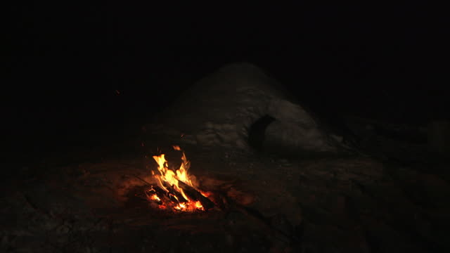 Static shot of a campfire burning in front of a snow cave, Yukon, Canada.