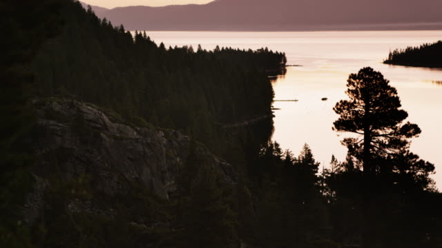 static shot of a cliff overlooking lake tahoe at sunset. - sunset bay state park stock videos & royalty-free footage